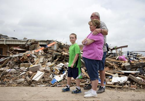 Julie Lewis watches with her husband Scott Lewis, and their son Zack, as President Barack Obama moves on with his tour of the devastation of Moore, Okla., after trying to comfort them Sunday, May 26, 2013. Zack was a third-grader at the Plaza Towers Elementary School, now reduced to rubble in the background after the devastating tornado and severe weather last week. (AP Photo/Carolyn Kaster)