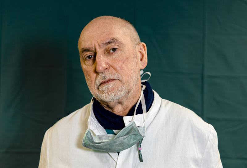 """Director of the Intensive Care unit Gabriele Tomasoni, 65, poses for a portrait at the Brescia Spedali Civic Hospital, in Brescia, Italy Friday, March 27, 2020. The intensive care doctors and nurses on the front lines of the coronavirus pandemic in Italy are almost unrecognizable behind their masks, scrubs, gloves and hairnets. """"These are patients who are starving for air,"""" said Tomasoni. """"We know these are elderly patients,"""" Tomasoni said at the end of his shift on Friday evening. """"They need closeness. Tenderness."""" (AP Photo/Luca Bruno)"""