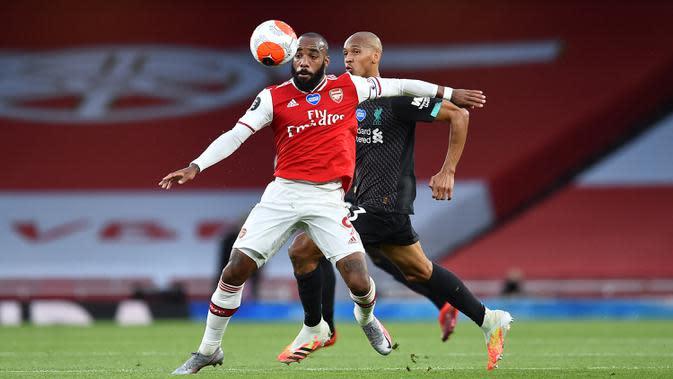 Striker Arsenal,Alexandre Lacazette, berebut bola dengan gelandang Liverpool, Fabinho, pada pada laga lanjutan Premier League pekan ke-36 di Emirates Stadium, Kamis (16/7/2020) dini hari WIB. Arsenal menang 2-1 atas Liverpool. (AFP/Glyn Kirk/pool)