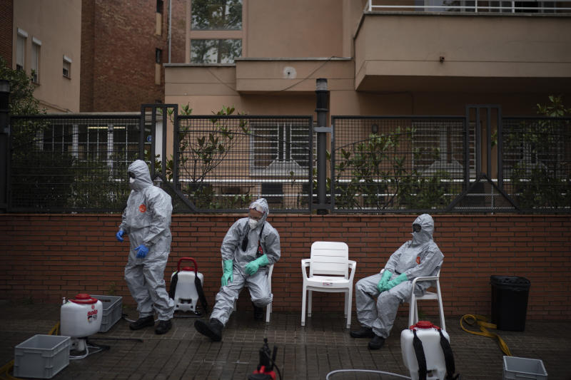 Ffirefighters wearing protective suits wait outside a nursing home before disinfecting it in efforts to prevent the spread of the new coronavirus in Barcelona, Spain, Monday, March 30, 2020. Governments in Europe's hardest-hit countries have yet to systematically test the residents of nursing homes or those who receive in-home care. In Spain, Italy and France, which together account for a third of the world's confirmed coronavirus cases, no one knows for sure how many people have become sick and died of coronavirus, especially among the elderly. The new coronavirus causes mild or moderate symptoms for most people, but for some, especially older adults and people with existing health problems, it can cause more severe illness or death. (AP Photo/Felipe Dana)