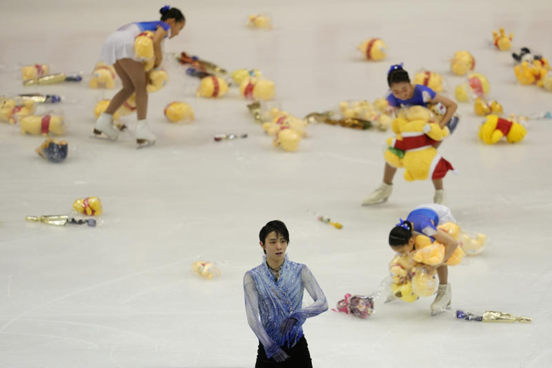 Yuzuru Hanyu of Japan acknowledges the crowd after his men's short program as skating girls collect flowers and toys thrown from fans during the ISU Grand Prix of Figure Skating in Sapporo, northern Japan, Friday, Nov. 22, 2019. (AP Photo/Toru Hanai)