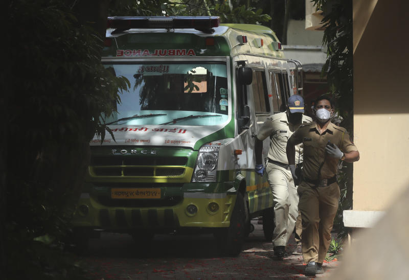 Policemen walk near an ambulance carrying the body of Bollywood actor Sushant Singh Rajput before it leaves from the building he lived in Mumbai, India, Sunday, June 14, 2020. Rajput was found dead at his Mumbai residence on Sunday, police and Indian media reports said. (AP Photo/Rafiq Maqbool)