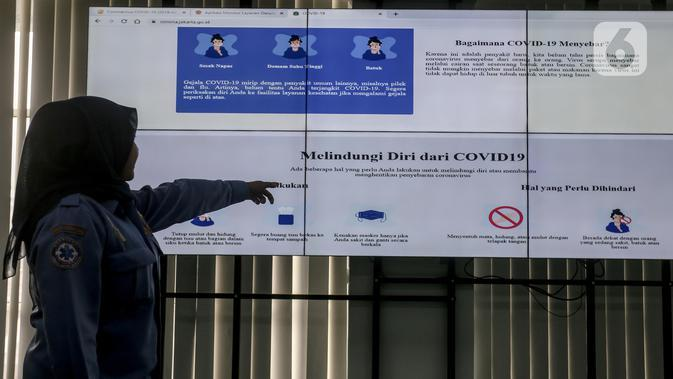 Petugas menunjukan penyebaran virus corona (COVID-19) pada layar pemantau di Dinas Kesehatan DKI Jakarta, Senin (9/3/2020). Sampai hari ini, Posko COVID-19 DKI Jakarta terlah dihubungi 3.580 orang. (Liputan6.com/Faizal Fanani)