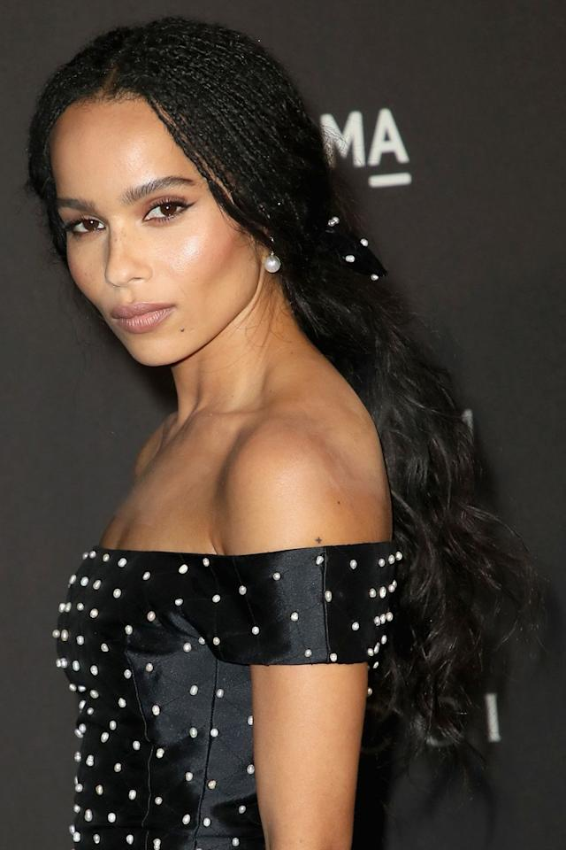 <p>Zoë Kravtiz wears her hair in box braids up top and loose curls on the bottom. For added glam, her hair is gathered and tied with a pearl-accented hair tie. </p>