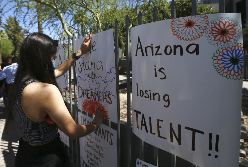Deya Garcia, Deferred Action for Childhood Arrivals recipient, tapes up a poster in front of the U.S. Immigration and Customs Enforcement building during a during a news conference after the U.S. Supreme Court ruled on the DACA program Thursday, June 18, 2020, in Phoenix. The U.S. Supreme Court ruled President Donald Trump improperly ended the program that protects immigrants brought to the country as children and allows them to legally work, keeping the people enrolled in DACA. (AP Photo/Ross D. Franklin)