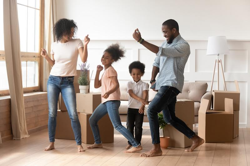 young black family dancing in living room