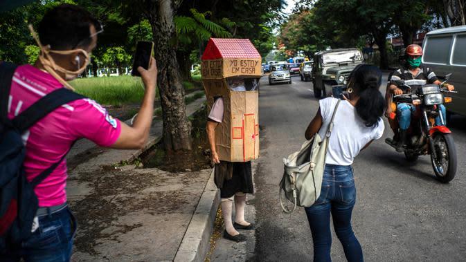Orang-orang mengambil gambar pensiunan perawat, Feridia Rojas yang memakai kotak kardus berbentuk rumah untuk melindungi dirinya dari penyebaran Covid-19 di Havana, Kuba, 8 Juli 2020. Pakaian pelindung kardus itu dipakai Rojas untuk melakukan aktivitas di luar rumah sehari-hari. (AP/Ramon Espinosa)