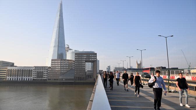 Pejalan kaki berjalan melewati London Bridge menuju Kota London di Inggris, Selasa (15/9/2020). Tingkat pengangguran di Inggris mengalami kenaikan untuk pertama kalinya sejak penerapan karantina wilayah (lockdown) pada Maret, data resmi menunjukkan pada Selasa (15/9). (JUSTIN TALLIS/AFP)