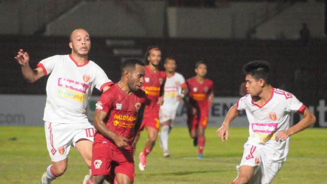 Pemain Kalteng Putra, Ferinando Pahabol (merah) mencoba melewati bek kiri Badak Lampung FC, Mustofa (kanan) dalam laga di Stadion Sultan Agung, Bantul, Selasa (28/5/2019) malam. (Bola.com/Vincentius Atmaja)