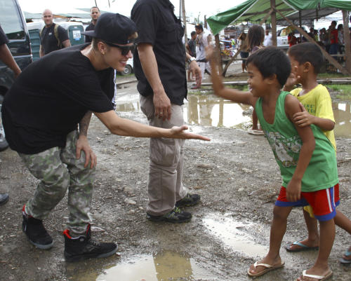 Justin Bieber, left, exchanges high-fives with children survivors of typhoon Haiyan during his visit Tuesday, Dec. 10, 2013 to Tacloban city, Leyte province in central Philippines. The teen heartthrob Bieber arrived Tuesday in the Philippines, where he has launched a campaign to help victims of last month's killer typhoon. (AP Photo)