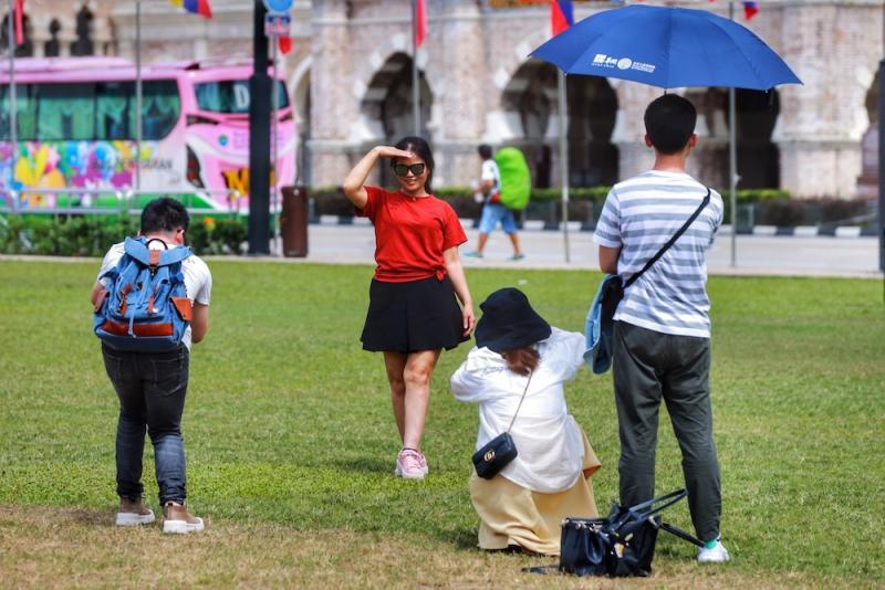 Tourists from China take pictures at Dataran Merdeka in Kuala Lumpur January 23, 2020. — Picture by Ahmad Zamzahuri