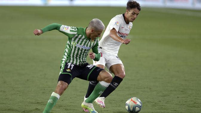 Gelandang Sevilla, Olivier Torres, berebut bola dengan gelandang Real Betis, Cristian Tello, pada laga lanjutan La Liga di Estadio Ramon Sanchez Pizjuan, Jumat (12/6/2020) dini hari WIB. Sevilla menang 2-0 atas Real Betis. (AFP/Cristina Quicler)