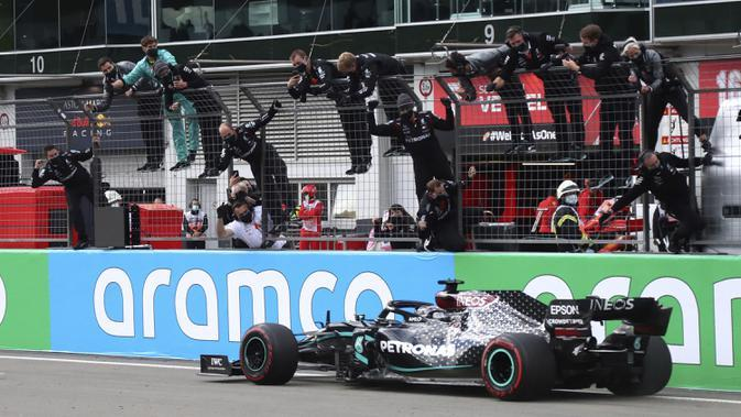 Pembalap Mercedes Lewis Hamilton melintasi garis finis untuk memenangkan F1 GP Eifel di Nuerburgring, Nuerburg, Jerman, Minggu (11/10/2020). Hamilton dengan 91 kemenangannya menyamai legenda F1 Michael Schumacher. (AP Photo/Matthias Schrader, Pool)