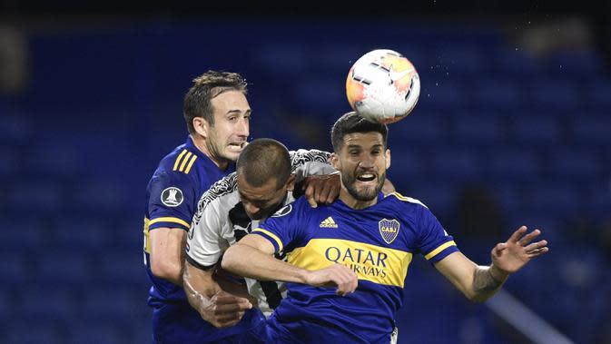 Penyerang Boca Juniors, Lisandro Lopez, berebut bola dengan bek Libertad, Paulo Da Silva, pada laga grup H Copa Libertadores di Estadio La Bombonera, Rabu (30/9/2020) dini hari WIB. Boca Juniors bermain imbang 0-0 atas Libertad. (Juan Mabromata/Pool via AP)