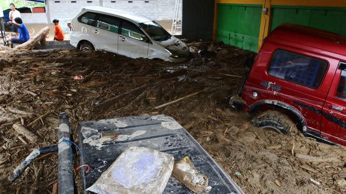 Mobil-mobil terjebak lumpur di daerah yang terkena banjir bandang di Masamba, Sulawesi Selatan, Rabu (15/7/2020). Banjir bandang yang terjadi akibat tingginya curah hujan itu mengakibatkan 16 orang meninggal dunia, sementara ratusan rumah rusak berat dan hilang. (AP/Khaizuran Muchtamir)
