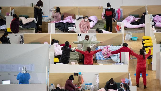 Petugas medis berjalan di antara pasien dengan gejala ringan virus corona COVID-19 yang beristirahat pada malam hari di stadion olahraga yang diubah menjadi rumah sakit darurat di Wuhan, 18 Februari 2020. Jumlah korban virus corona hingga Kamis (20/2) kembali meningkat menjadi 2.120 orang. (STR/AFP)