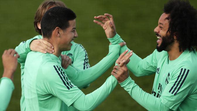 Bek Real Madrid, Marcelo (kanan) tertawa dengan penyerang James Rodriguez selama sesi latihan tim di Valdebebas di Madrid, Spanyol, Selasa, (25/2/2020). Real Madrid akan menjamu wakil Inggris, Manchester City pada leg pertama babak 16 besar Liga Champions di Bernabeu. (AP Photo/Manu Fernandez)