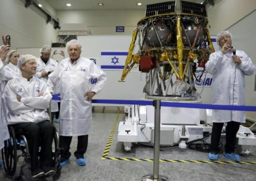 Israeli Aerospace Industries director of Space division Opher Doron (R) and billionaire investor Morris Kahn (2nd-R) present a spacecraft during a press conference to announce its launch to the moon, in Yehud, central Israel