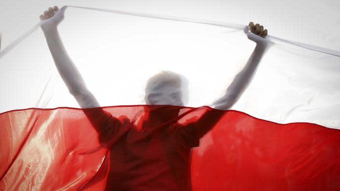 Demonstran digambarkan siluet oleh bendera nasional Belarusia tua saat unjuk rasa di Minsk, Belarus, Minggu (4/10/2020). Ratusan ribu warga Belarusia telah melakukan protes setiap hari sejak 9 Agustus pemilihan presiden. (AP Photo)