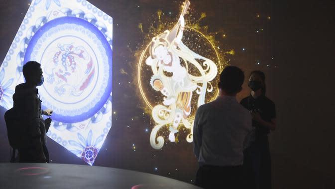 Staf (kanan) menjelaskan konten yang dipamerkan kepada sejumlah pengunjung di sebuah pameran digital dalam pratinjau media di Museum Ibu Kota (Capital Museum), Beijing, China, 25 September 2020. Pameran ini menampilkan konten-konten digital peninggalan sejarah dari sejumlah museum. (Xinhua/Lu Peng)