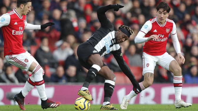 Pemain Newcastle United, Allan Saint-Maximin mengontrol bola dari kawalan dua pemain Arsenal, Hector Bellerin dan Mesut Ozil pada pertandingan lanjutan Liga Inggris di Stadion Emirates di London, Minggu, (16/2/2020). Arsenal menang telak 4-0 atas Newcastle. (AP Photo/Frank Augstein)