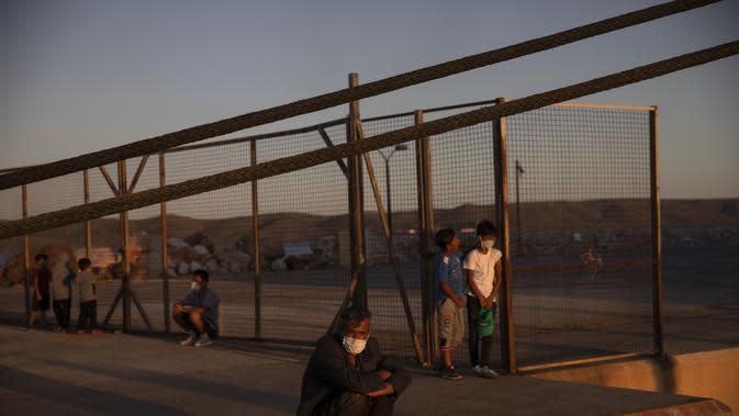 Pengungsi dan migran yang mengenakan masker pelindung untuk membantu mencegah penyebaran virus corona menunggu untuk naik bus setelah kedatangan mereka di pelabuhan Lavrio, sekitar 75 kilometer (48 mil) selatan Athena (29/9/2020). (AP Photo/Petros Giannakouris)