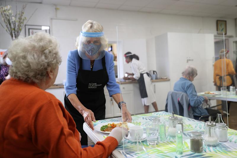 Britain's Camilla, Duchess of Cornwall, in her role as President, Royal Voluntary Service, wears a facemask and faceshield as she serves lunch to Doris Winfield, 86, during her visit to the Royal Voluntary Service Mill End lunch club in Rickmansworth, Hertfordshire on October 8, 2020, to meet volunteers who have overcome recent challenges posed by the novel coronavirus COVID-19 pandemic to reinstate the much-needed lunch sessions. (Photo by Andrew Matthews / POOL / AFP) (Photo by ANDREW MATTHEWS/POOL/AFP via Getty Images)