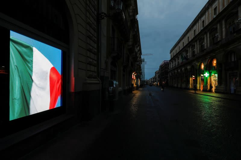 A screen displaying the Italian flag is pictured on an empty street, after Italy reinforced the lockdown measures to combat the coronavirus disease (COVID-19) in Catania, Italy March 21, 2020. REUTERS/Antonio Parrinello