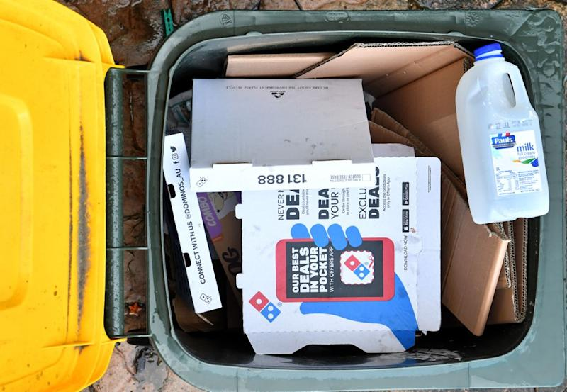 Yellow top recycling bin filled with cardboard, a pizza box and milk bottle.
