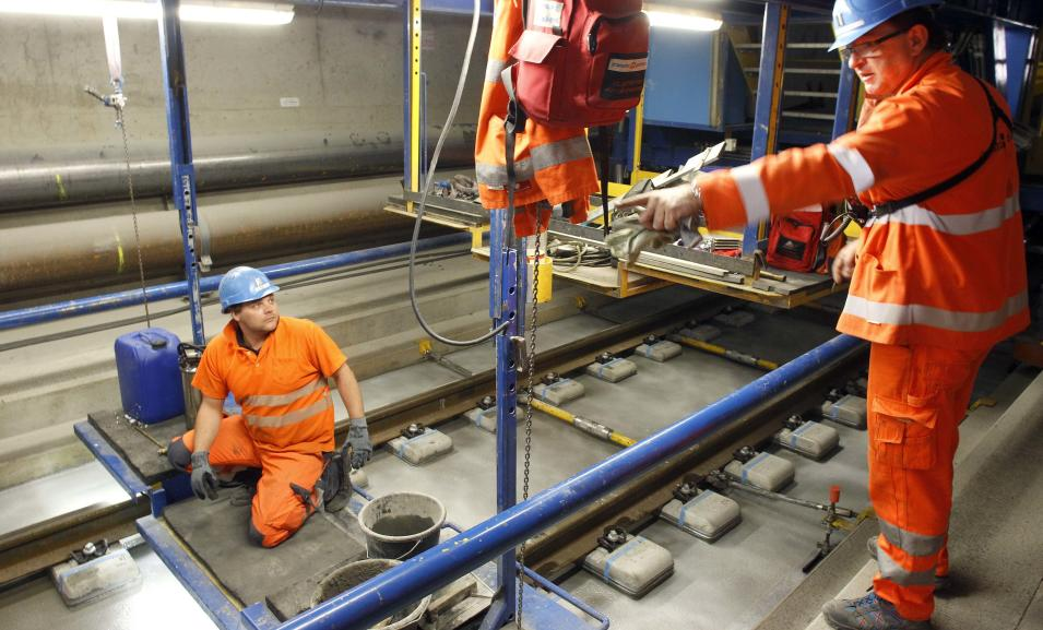 A worker receives instructions from an engineer during the installation of the railway tracks in the NEAT Gotthard Base tunnel near Erstfeld