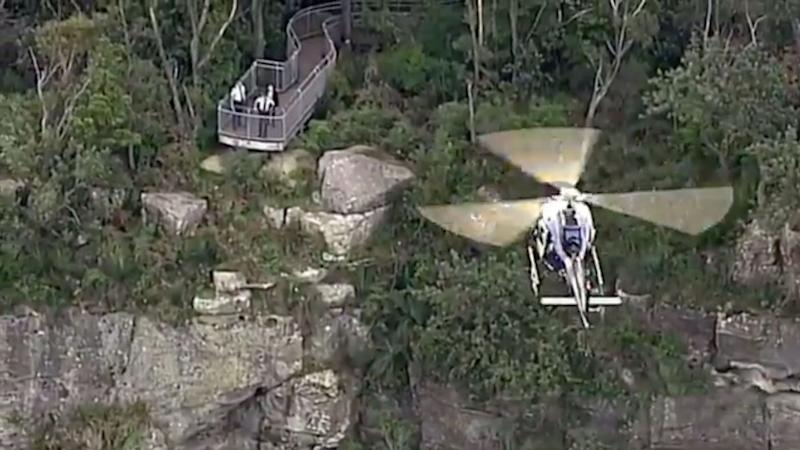 The cliff edge where the mum and her toddler died at Mt Keira is seen on Tuesday. Police stand at the lookout while a helicopter flies over.