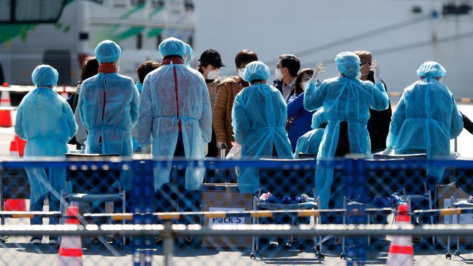 Petugas memeriksa penumpang yang turun dari kapal pesiar Diamond Princess yang dikarantina di Yokohama, Jepang, Jumat (21/2/2020). Dua orang Jepang dari kapal pesiar Diamond Princess dilaporkan meninggal dunia. (AP Photo/Eugene Hoshiko)