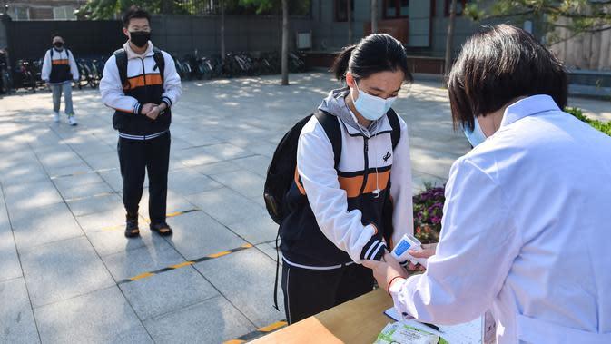 Sejumlah siswa mengantre sambil menjaga jarak untuk menjalani pemeriksaan suhu tubuh di Sekolah Menengah Atas No. 161 Beijing, Beijing, China, Senin (27/4/2020). Sekolah menengah atas di Beijing memulai kembali kegiatan belajar di kelas untuk siswa tingkat akhir. (Xinhua/Peng Ziyang)