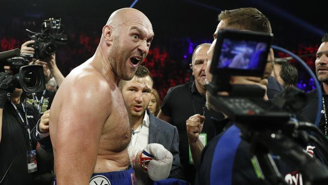 Petinju Inggris Tyson Fury merayakan kemenangan atas Tom Schwarz, dari Jerman dalam pertandingan tinju kelas berat di Las Vegas, Minggu (16/6/2019). (Foto AP / John Locher)