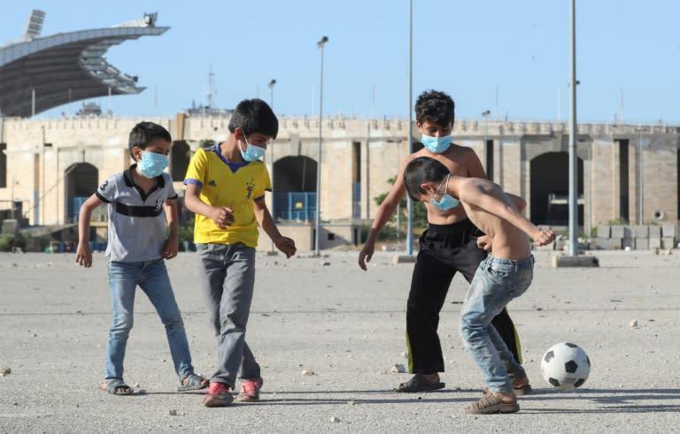 Mask-clad boys play football in the Lebanese capital Beirut