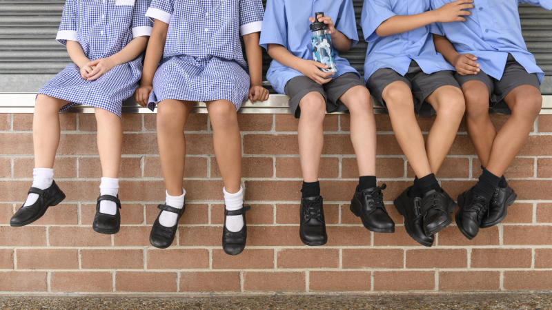 Children's legs and feet in black shoes hanging down in a stock photo. Ipswich West State School has apologised for accidentally sending home a fact sheet to parents about safe sex following a skin infection going around the school.