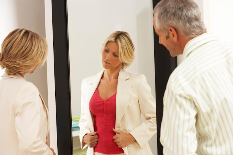 woman looking at outfit in mirror