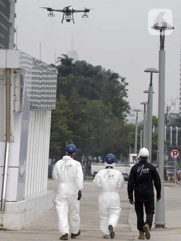 Petugas menggunakan drone saat menyemprotkan cairan disinfektan di Jalan Bursa Efek menuju Patung Pemuda, Jakarta, Jumat (27/3/2020). Penyemprotan dilakukan untuk mencegah penyebaran virus corona COVID-19. (merdeka.com/Imam Buhori)