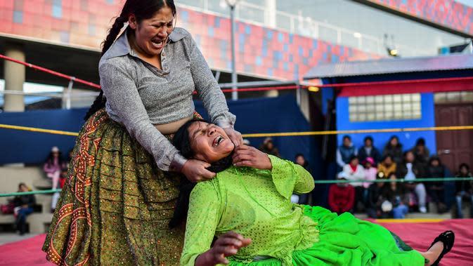 Pegulat Bolivia, Ana Luisa Yujra (kiri), bertarung dengan lawannya, Lidia Flores di atas ring gulat di El Alto, pada 24 November 2019. Di Bolivia ada sebuah atraksi gulat yang diperankan perempuan dengan menggunakan busana khas warga Bolivia. (Ronaldo SCHEMIDT / AFP)