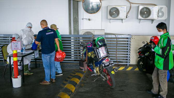 Petugas Hotel Ibis Styles Mangga Dua Square Jakarta menerima barang kiriman untuk pasien Covid-19 berstatus orang tanpa gejala (OTG) yang sedang melakukan isolasi mandiri, Kamis (1/10/2020). Dalam menjalankan tugasnya, petugas hotel selalu memakai APD lengkap. (Liputan6.com/Faizal Fanani)