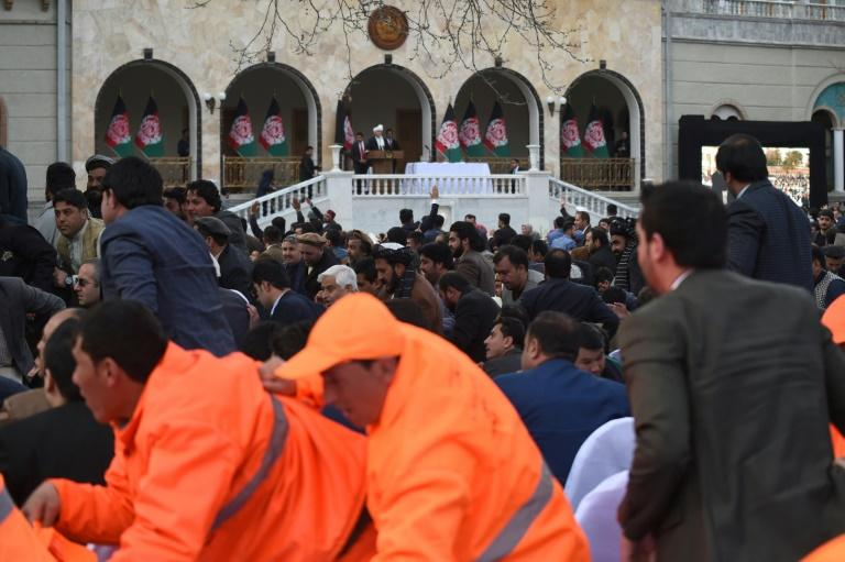 Officials and guests react after hearing loud blasts during Afghan President Ashraf Ghani's inauguration ceremony -- but he refused to leave the podium
