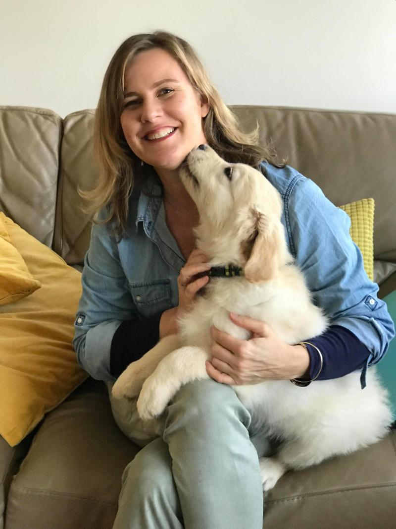 Dr Leigh Davidson sits on a couch holding a dog that is licking her chin.