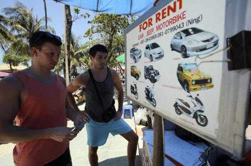 In this March 13, 2014 photo, German tourist Falko Tillwich, left, holds his passport near his German friend, who didn't want to give his name as they try to contact a car rental on Pathong Beach in Phuket province, southern Thailand. Thailand's sapphire blue waters, wildlife parks, delicious cuisine and raunchy red light districts have attracted tourists for decades. Phuket is one of Thailand's tourism honeypots. Tourists flock here in droves each year for its sun, sand and laid back ambience. And some lose their passports along the way. (AP Photo/Sakchai Lalit)