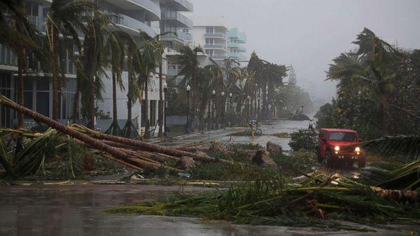 PHOTO: A vehicle passes downed palm trees and two cyclists attempt to ride as Hurricane Irma passes through the area on Sept. 10, 2017 in Miami Beach, Fla. (Joe Raedle/Getty Images)