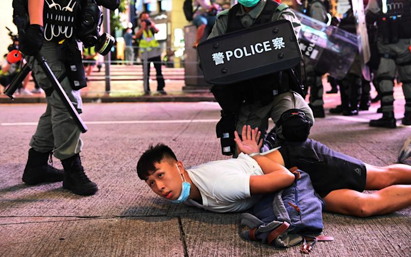 Police officers detain protesters during a rally against a new national security law - MIGUEL CANDELA/EPA-EFE/Shutterstock