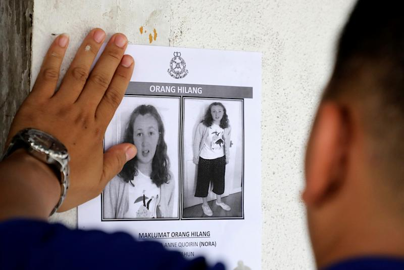 A police officer pastes a photo of 15-year-old Irish girl Nora Anne Quoirin who went missing from a resort on a wall at a shop in Seremban August 9, 2019.