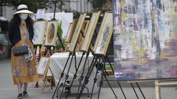 Seorang wanita mengamati karya seni yang dipajang di area terbuka dalam pameran Art Downtown, Vancouver, British Columbia, Kanada, 4 September 2020. Art Downtown merupakan proyek yang memungkinkan seniman dan publik saling terhubung dan menginspirasi serta berbagi kreativitas. (Xinhua/Liang Sen)