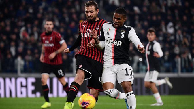 Bek AC Milan, Leo Duarte, berebut bola dengan gelandang Juventus, Douglas Costa, pada laga Serie A Italia di Stadion Allianz, Turin, Minggu (10/11). Juventus menang 1-0 atas Milan. (AFP/Marco Bertorello)