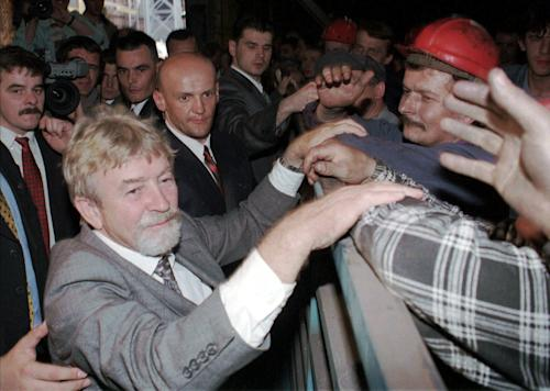 In this file photo from April 30 1998, Poland's Cold War spy, Ryszard Kuklinski greets steel mill workers in Nowa Huta, southern Poland. From behind the Iron Curtain, Kuklinski passed some 35,000 pages of Warsaw Pact secrets to the CIA, including the communist government's plan to impose martial law in 1981 and launch a brutal crackdown on the pro-democracy Solidarity movement. He was spirited out of Poland with his wife and two sons shortly before the Dec. 13, 1981 military crackdown, and the family lived in hiding in the U.S. Poland's military court sentenced him to death for treason and desertion. The charges were lifted in 1998 and Kuklinski came on a visit.(AP Photo/Czarek Sokolowski)