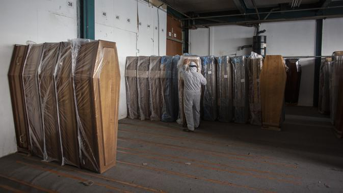 Pekerja menata peti mati di sebuah perusahaan di Ris Orangis, Prancis, Selasa (14/4/2020). Hingga saat ini, Prancis secara resmi mencatat lebih dari 15 ribu kematian akibat infeksi virus corona COVID-19. (AP Photo/Rafael Yaghobzadeh)